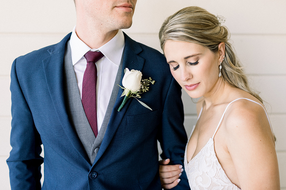 red-barn-wedding-close-up-on-bride-and-groom-grooms-face-cut-out-of-frame-bride-in-a-lace-fitted-dress-with-thin-straps-groom-in-a-blue-suit-with-grey-vest-and-burgundy-tie