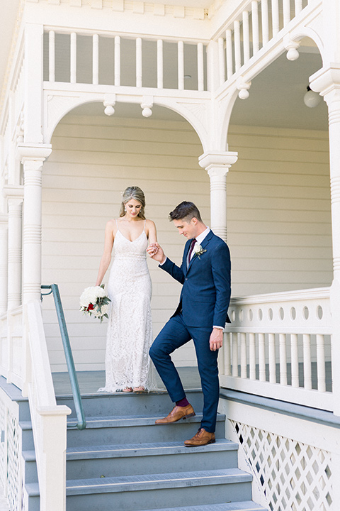 red-barn-wedding-bride-and-groom-walking-down-steps-of-white-building-bride-in-a-lace-fitted-dress-with-thin-straps-groom-in-a-blue-suit-with-grey-vest-and-burgundy-tie