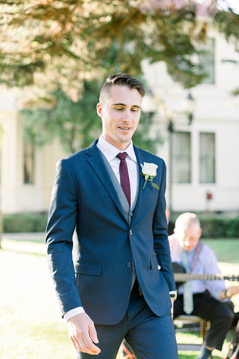 red-barn-wedding-groom-walking-down-ceremony-aisle-groom-in-a-blue-suit-with-grey-vest-and-burgundy-tie