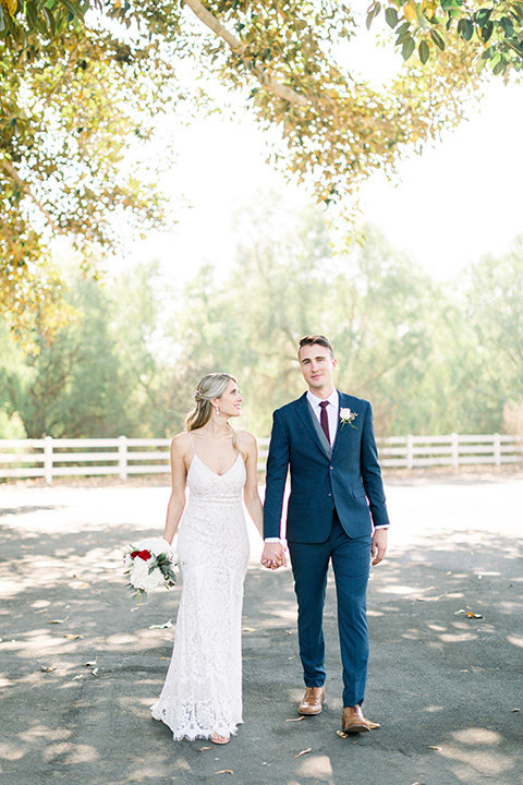 red-barn-wedding-bride-and-groom-walking-bride-in-a-lace-fitted-dress-with-thin-straps-groom-in-a-blue-suit-with-grey-vest-and-burgundy-tie