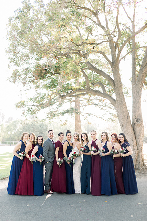 red-barn-wedding-bridesmaids-bridesmaids-in-alternating-navy-and-burgundy-dresses-groomsmen-in-grey-suits-bride-in-a-lace-fitted-dress-with-thin-straps-groom-in-a-blue-suit-with-grey-vest-and-burgundy-tie