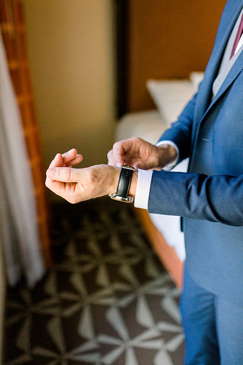 red-barn-wedding-chris-fixing-his-watch-groom-in-a-blue-suit-with-grey-vest-and-burgundy-tie