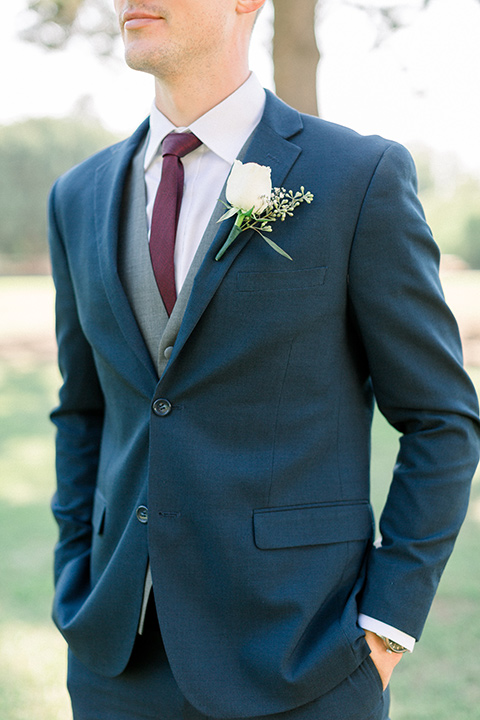 red-barn-wedding-close-up-on-groom-groom-in-a-blue-suit-with-grey-vest-and-burgundy-tie