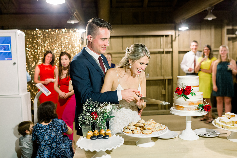 red-barn-wedding-cutting-the-cake-bride-in-a-lace-fitted-dress-with-thin-straps-groom-in-a-blue-suit-with-grey-vest-and-burgundy-tie