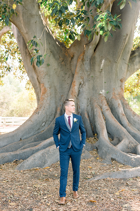 red-barn-wedding-groom-by-tree-groom-in-a-blue-suit-with-grey-vest-and-burgundy-tie