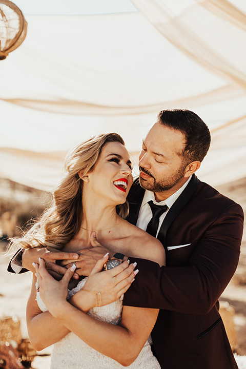 Bohemian-Desert-Shoot-bride-and-groom-holding-each-other-bride-in-a-formfitting-lace-gown-with-a-strapless-neckline-groom-in-a-burgundy-shawl-lapel-tuxedo-with-a-black-long-lie