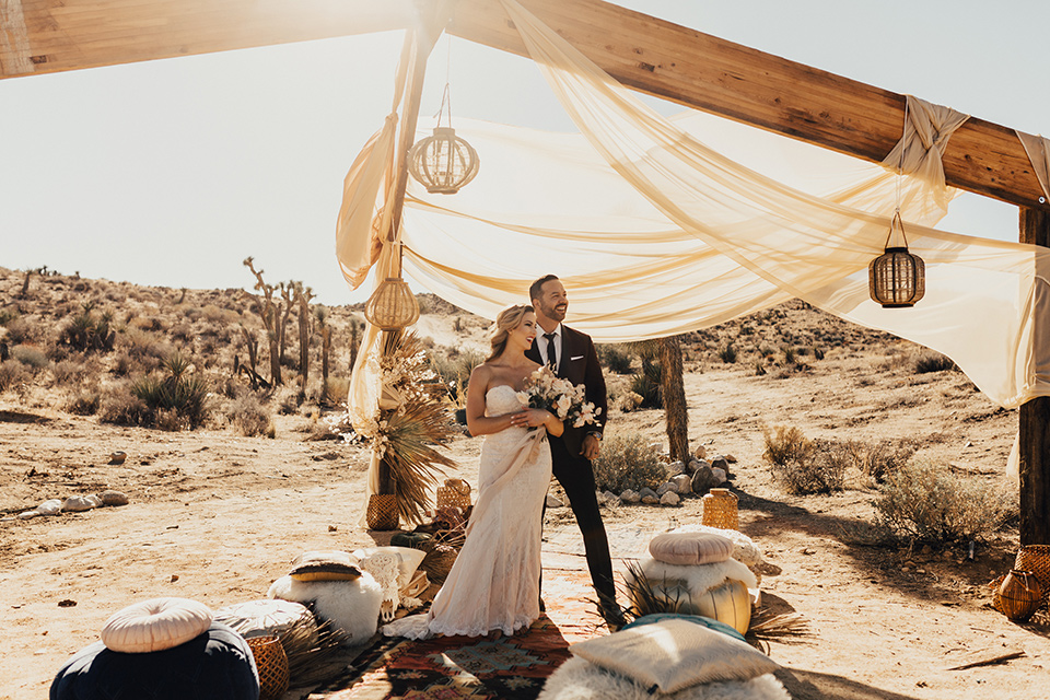 Bohemian-Desert-Shoot-bride-and-groom-in-ceremony-space-bride-in-a-formfitting-gown-with-lace-detailing-and-a-sweetheart-neckline-groom-in-a-burgundy-shawl-lapel-tuxedo-with-a-black-long-tie