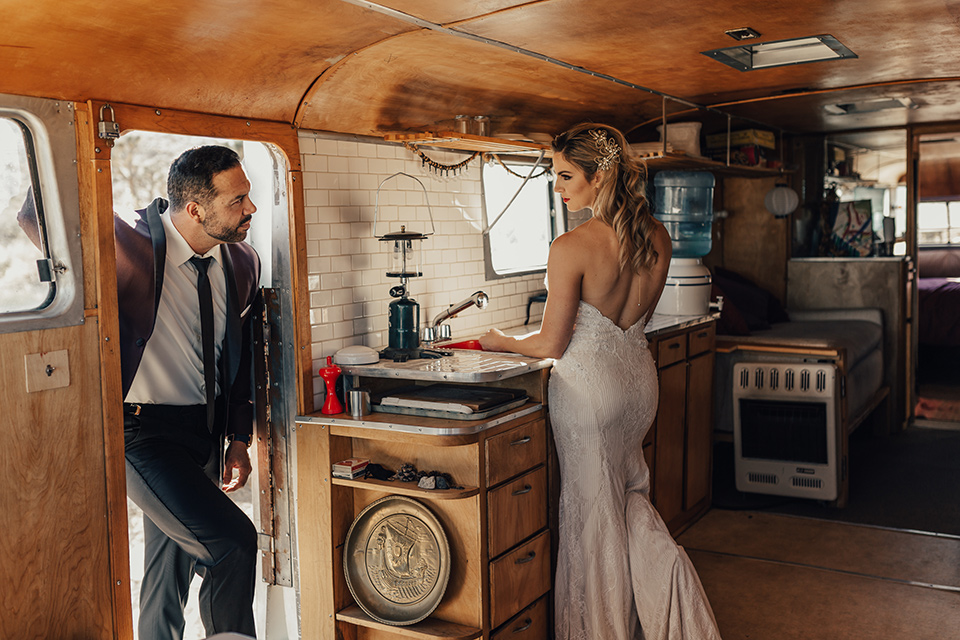 Bohemian-Desert-Shoot-bride-and-groom-in-rv-bride-in-a-formfitting-gown-with-lace-detailing-and-a-sweetheart-neckline-groom-in-a-burgundy-shawl-lapel-tuxedo-with-a-black-long-tie