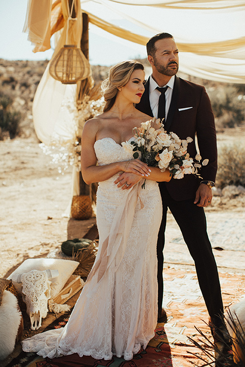 Bohemian-Desert-Shoot-bride-and-groom-looking-away-from-camera-bride-in-a-lace-formfitting-gown-with-a-sweetheart-neckline-groom-in-a-burgundy-shawl-lapel-tuxedo-with-a-black-long-tie