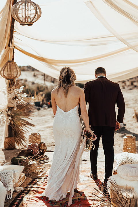 Bohemian-Desert-Shoot-bride-and-groom-moving-away-from-camera-bride-in-a-lace-formfitting-gown-with-a-sweetheart-neckline-groom-in-a-burgundy-shawl-lapel-tuxedo-with-a-black-long-tie
