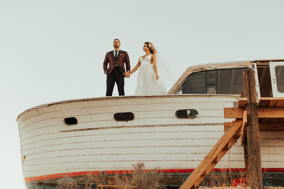 Bohemian-Desert-Shoot-bride-and-groom-on-boat-bride-in-a-formfitting-gown-with-lace-detailing-and-a-sweetheart-neckline-groom-in-a-burgundy-shawl-lapel-tuxedo-with-a-black-long-tie