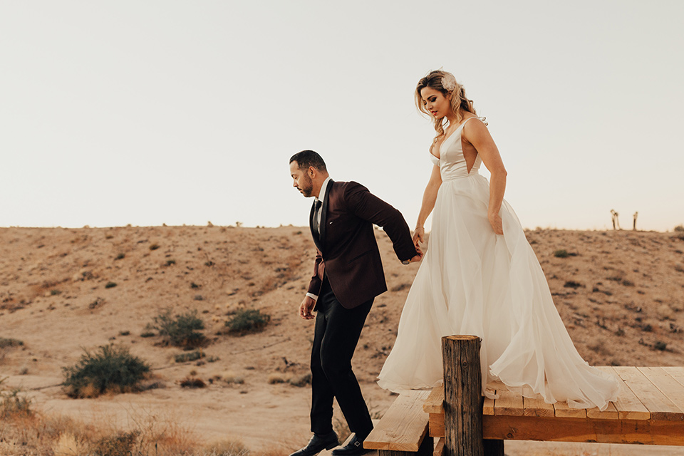 Bohemian-Desert-Shoot-bride-and-groom-walking-down-steps-bride-in-a-formfitting-gown-with-lace-detailing-and-a-sweetheart-neckline-groom-in-a-burgundy-shawl-lapel-tuxedo-with-a-black-long-tie