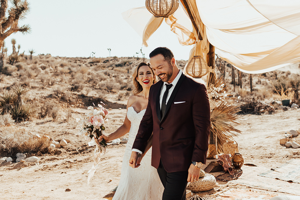 Bohemian-Desert-Shoot-bride-and-groom-walking-towards-camera-bride-in-a-formfitting-gown-with-lace-detailing-and-a-sweetheart-neckline-groom-in-a-burgundy-shawl-lapel-tuxedo-with-a-black-long-tie