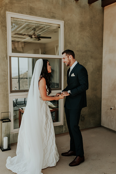 Dragon-point-villa-wedding-bride-and-groom-first-look-bride-in-a-white-ball-gown-with-sleeves-and-straps-groom-in-a-slim-black-suit-with-a-white-tie