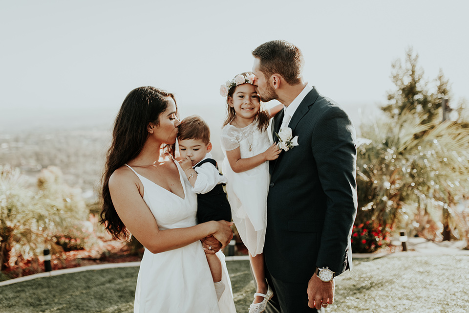 Dragon-point-villa-wedding-bride-and-groom-kissing-their-children-bride-in-a-white-ballgown-with-pockets-and-thin-straps-groom-in-a-black-suit-with-a-white-tie