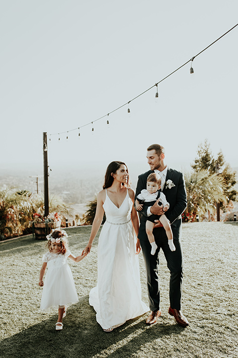 Dragon-point-villa-wedding-bride-and-groom-walking-with-the-kids-bride-in-a-white-ball-gown-with-pockets-and-thin-straps-groom-in-a-black-suit-and-white-tie