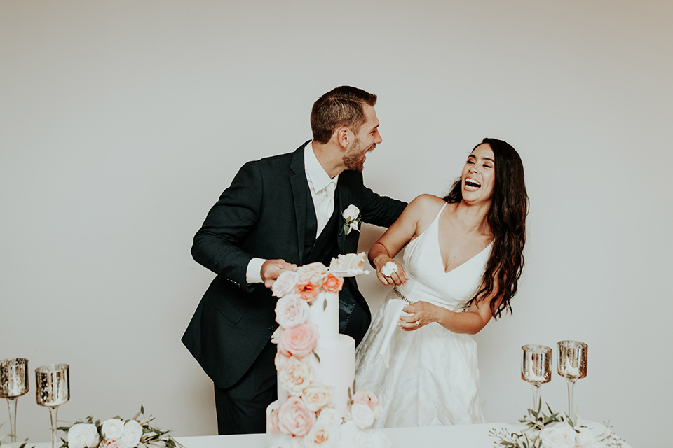 Dragon-point-villa-wedding-bride-and-groom-with-cake-smashed-in-their-faces-cake-bride-in-a-white-ballgown-with-pockets-and-thin-straps-groom-in-a-black-suit-with-a-white-tie