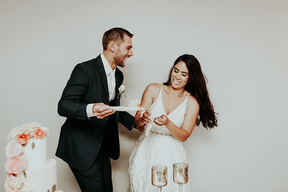 Dragon-point-villa-wedding-bride-and-groom-with-cake-bride-in-a-white-ballgown-with-pockets-and-thin-straps-groom-in-a-black-suit-with-a-white-tie