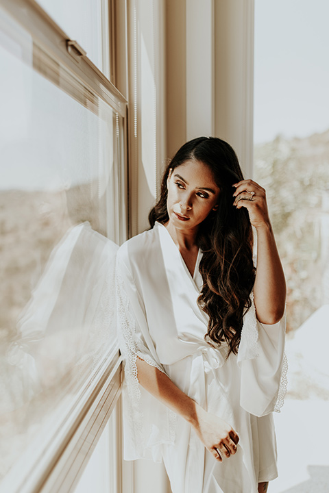 Dragon-point-villa-wedding-bride-looking-out-window-in-a-white-silk-robe
