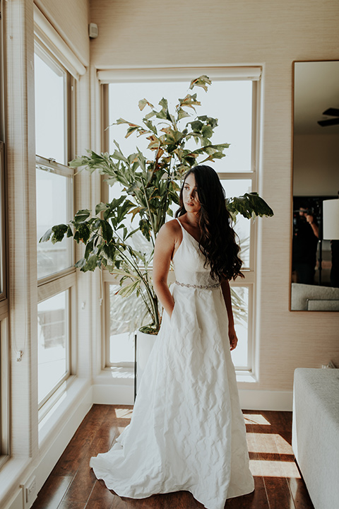 Dragon-point-villa-wedding-bride-with-hand-in-pocket-in-a-white-ball-gown-with-pockets-and-thin-straps
