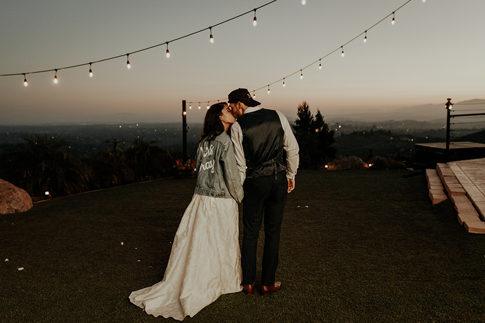 Dragon-point-villa-wedding-bride-with-jean-jacket-groom-with-hat-bride-in-a-white-ballgown-with-pockets-and-thin-straps-and-a-jean-jacket-groom-in-a-black-suit-with-a-white-tie