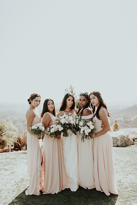 Dragon-point-villa-wedding-bridesmaids-looking-at-camera-bride-in-a-white-ball-gown-with-pockets-and-bridesmaids-in-light-pink-long-dresses