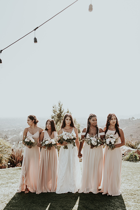 Dragon-point-villa-wedding-bridesmaids-looking-serious-bride-in-a-white-ball-gown-with-pockets-and-thin-straps-bridesmaids-in-long-blush-dresses