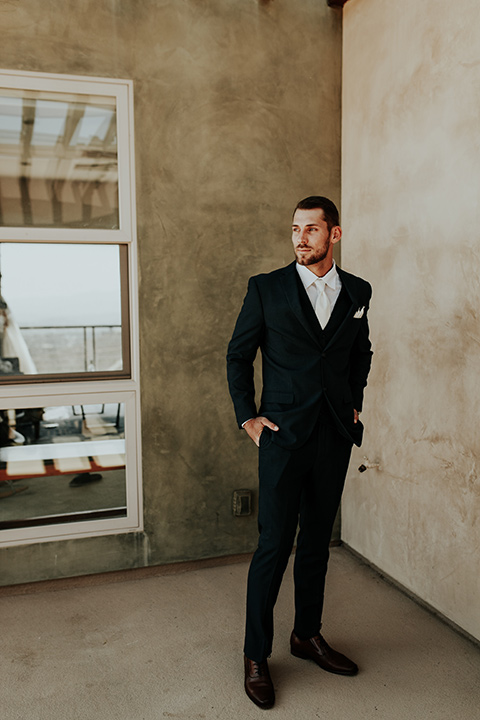 Dragon-point-villa-wedding-groom-standing-on-balcony-in-a-black-suit-and-white-tie