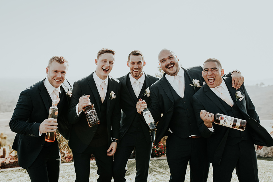 Dragon-point-villa-wedding-groomsmen-holding-alcohol-bottles-groom-and-groomsmen-in-black-suits-groomsmen-with-pink-ties-groom-with-a-white-tie