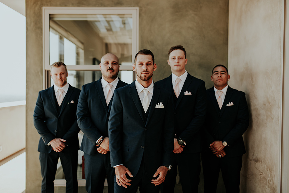 Dragon-point-villa-wedding-groomsmen-in-black-suits-with-light-pink-ties-and-groom-in-a-white-tie