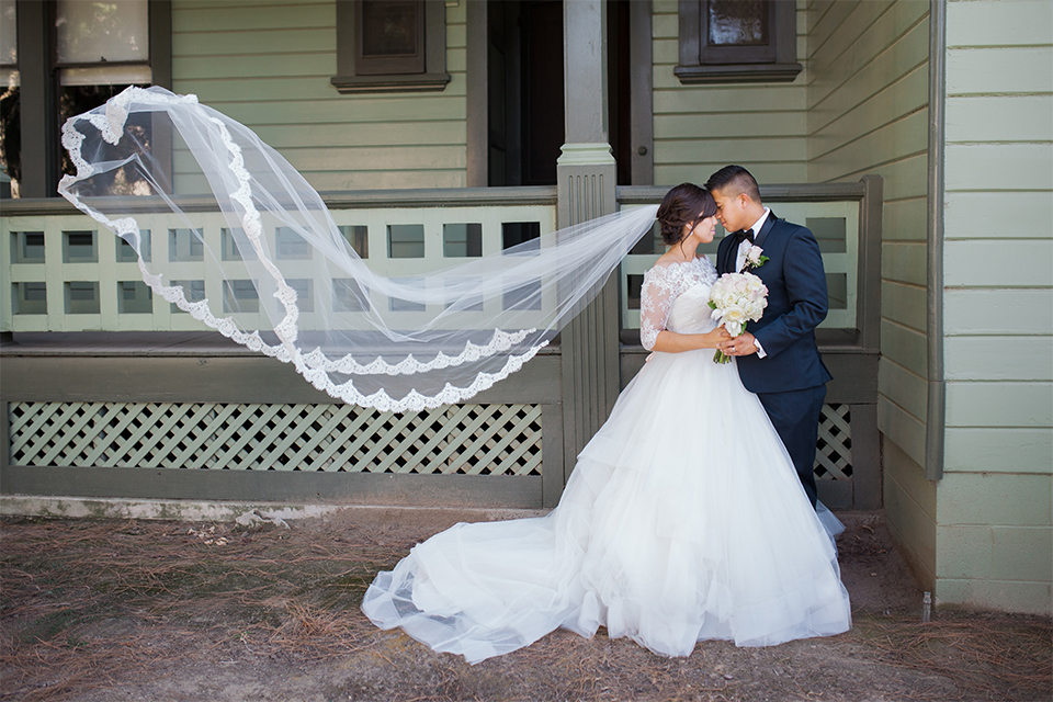 Elements-Venue-presents-wedding-bride-and-groom-outside-with-veil-in-the-wind-bride-is-in-a-layered-tulle-ball-gown-with-a-high-neckline-and-quarter-sleeves-groom-in-a-navy-blue-shawl-lapel-tuxedo-with-a-black-bow-tie