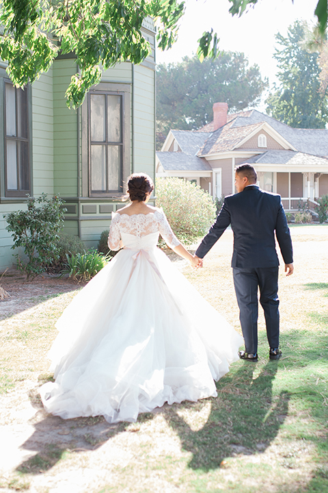 """Elements-Venue-presents-wedding-bride-and-groom-walking-away-bride-is-in-a-layered-tulle-ball-gown-with-a-high-neckline-and-quarter-sleeves-groom-in-a-navy-blue-shawl-lapel-tuxedo-with-a-black-bow-tie"""