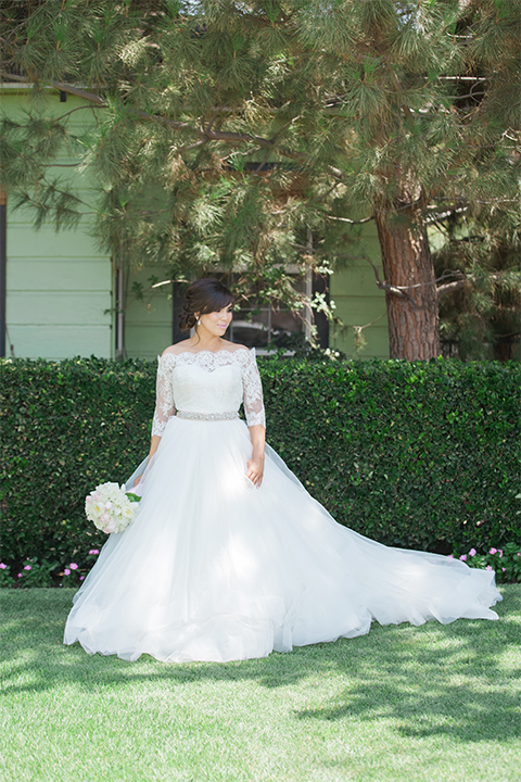 Elements-Venue-presents-wedding-bride-holding-flowers-in-a-layered-tulle-ball-gown-with-a-high-neckline-and-quarter-sleeves