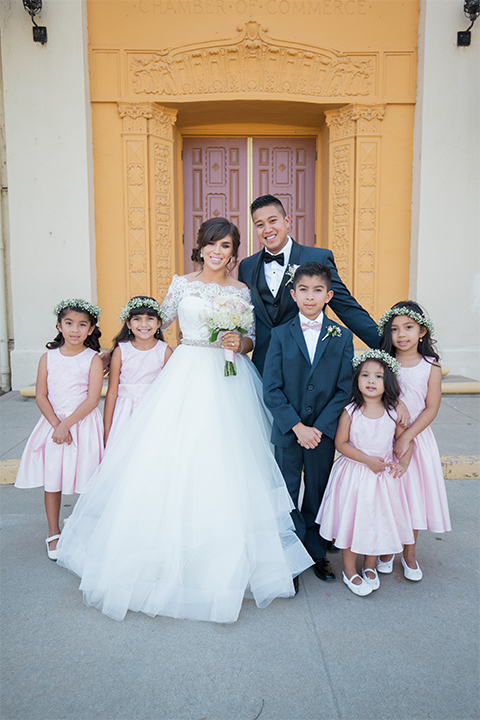 Elements-Venue-presents-wedding-flower-girls-and-ringbarers-in-pink-gowns-ringbarers-in-navy-suits-with-pink-long-ties-bride-is-in-a-layered-tulle-ball-gown-with-a-high-neckline-and-quarter-sleeves-groom-in-a-navy-blue-shawl-lapel-tuxedo-with-a-black-bow-tie