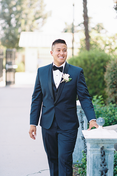 """Elements-Venue-presents-wedding-groom-walking-in-a-navy-blue-shawl-lapel-tuxedo-with-a-black-bow-tie"""