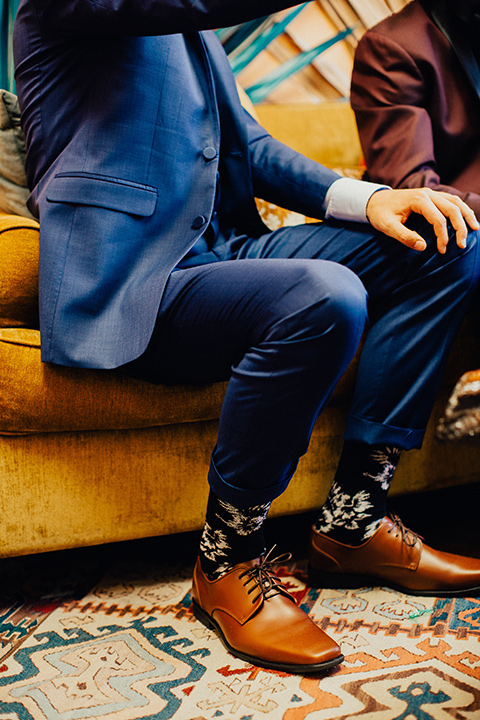 disco style wedding photo of man's feet with blue suit pants and floral socks