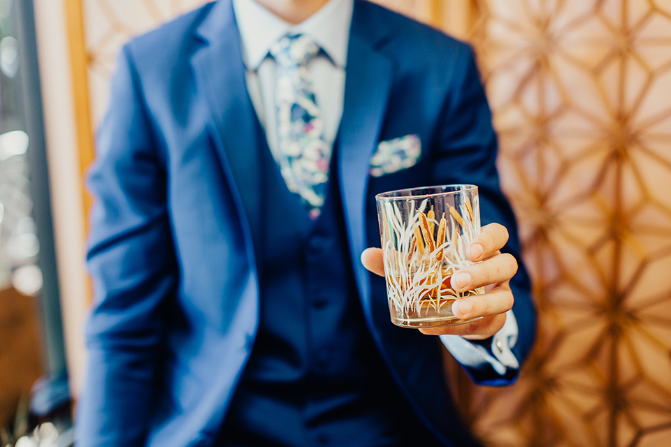Disco style wedding blue suit up close while holding whiskey glass