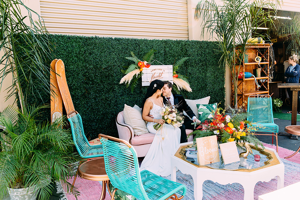 bride and groom sitting on outside furniture long shot the bride wore a from fitting white gown with lace detailing and a deep v neckline the groom is in a black velvet tuxedo with a peak lapel and burgundy long tie