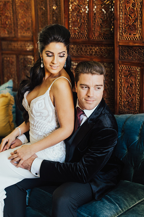 bride sitting on grooms lap with the bride wearing a form fitting white gown with lace detailing and a deep v neckline the groom wore a black velvet tuxedo with a peak lapel and burgundy long tie
