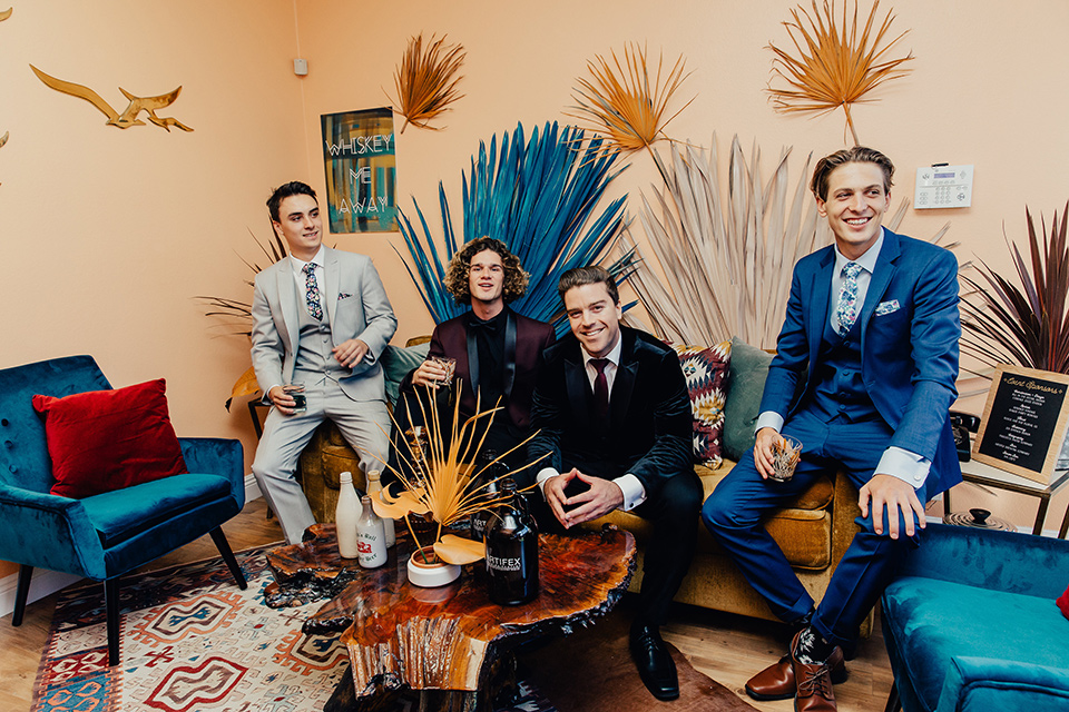 Groom and groomsmen posing for a picture on a couch wearing suits
