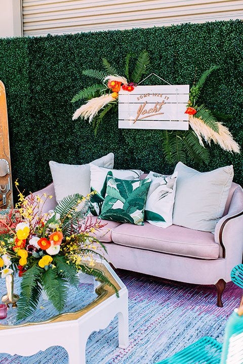 Disco style wedding outside furniture with a light pink retro inspired couch and tropical like decor