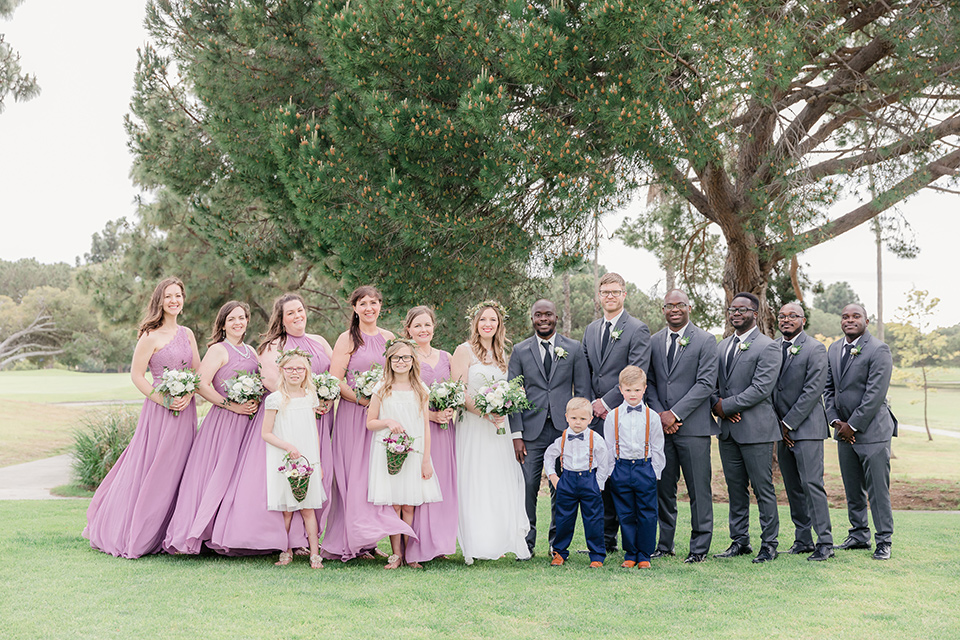 Los-Verdes-Golf-Course-Wedding-bridal-party-bridesmaids-in-pink-flowing-gowns-groomsmen-in-charcoal-tuxedos-with-black-ties-bride-in-a-white-gown-with-cap-sleeves-groom-in-a-charcoal-tuxedo-with-a-black-tie