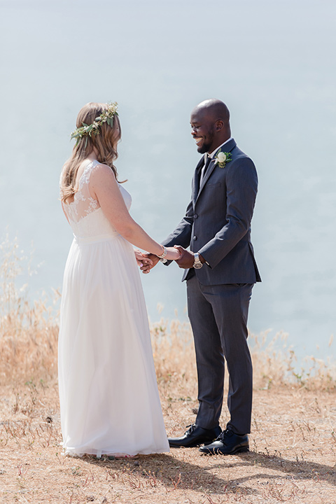 Los-Verdes-Golf-Course-Wedding-bride-and-groom-holding-hands-overlooking-the-ocean-bride-in-a-white-gown-with-cap-sleeves-groom-in-a-charcoal-tuxedo-with-a-black-tie