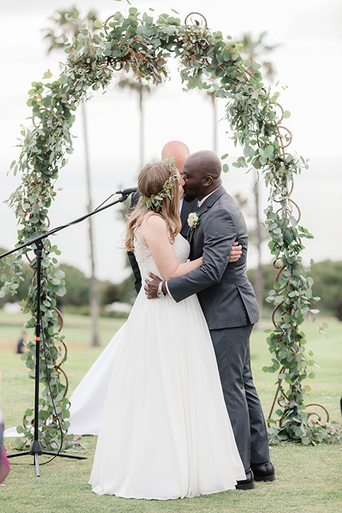 Los-Verdes-Golf-Course-Wedding-bride-and-groom-kissing-at-ceremony-bride-in-a-white-gown-with-cap-sleeves-groom-in-a-charcoal-tuxedo-with-a-black-tie