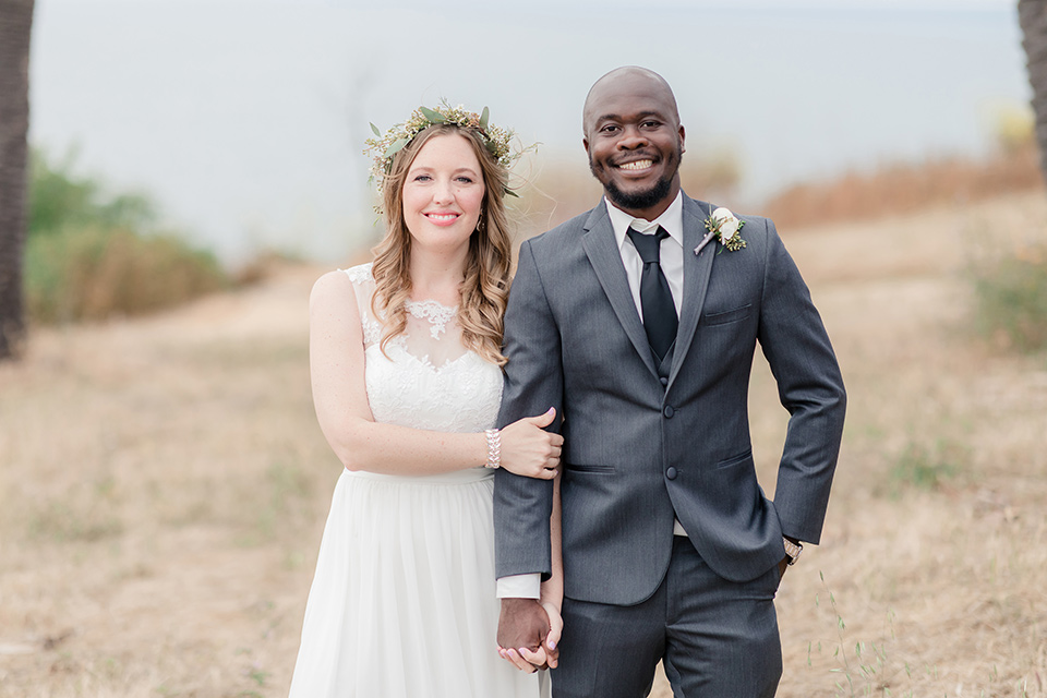Los-Verdes-Golf-Course-Wedding-bride-and-groom-smiling-at-camera-bride-in-a-white-gown-with-cap-sleeves-groom-in-a-charcoal-tuxedo-with-a-black-tie