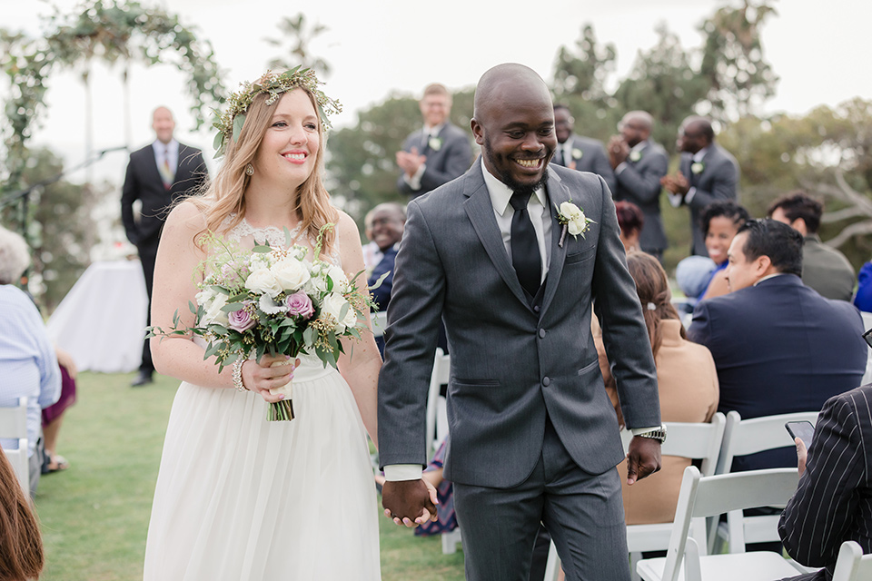 Los-Verdes-Golf-Course-Wedding-bride-and-groom-walking-down-aisle-bride-in-a-white-gown-with-cap-sleeves-groom-in-a-charcoal-tuxedo-with-a-black-tie