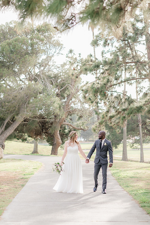 Los-Verdes-Golf-Course-Wedding-bride-and-groom-walking-towards-the-camera-bride-in-a-white-gown-with-cap-sleeves-groom-in-a-charcoal-tuxedo-with-a-black-tie