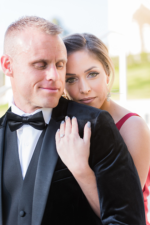 bride in a red evening gown with a plunging neckline and hair in a bun, groom in a black velvet tuxedo and black bow tie