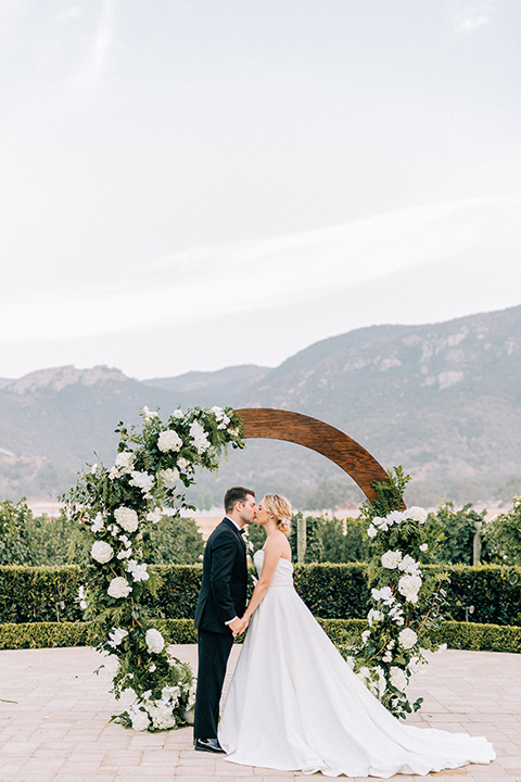 bride and groom by rounded ceremony arch with flowers on it, bride in a white strapless ballgown with a bow detail and hair in a bun, groom in a black tuxedo with a black bow tie