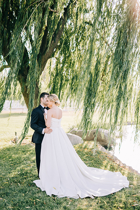 bride and groom willow tree, bride in a white strapless ballgown with a bow detail and hair in a bun, groom in a black tuxedo with a black bow tie